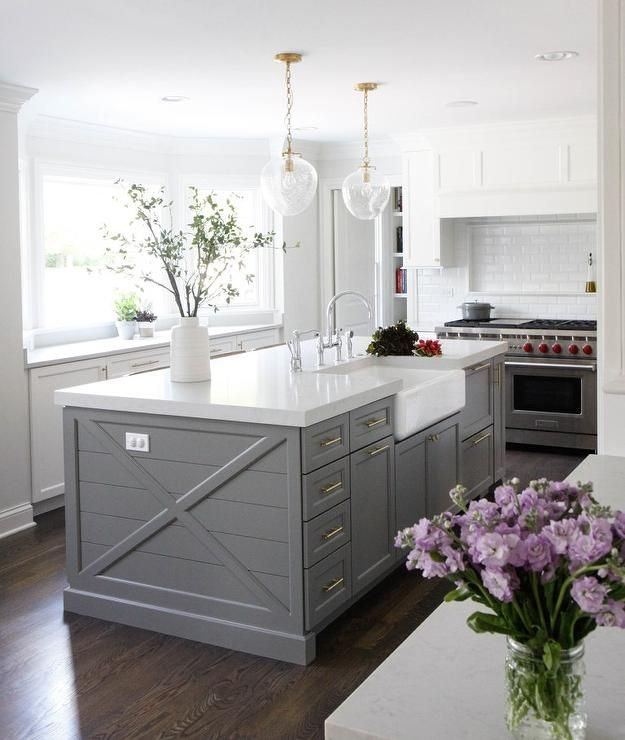 Beautifully designed gray shiplap center island is accented with brass cabinet pulls and a farmhouse sink with a polished nickel deck mount gooseneck faucet fixed to a thick white quartz lit by Katie Acorn Pendants.