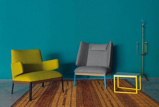 Sala com parede azul e poltronas cinza e amarela