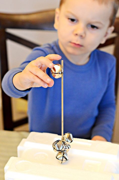 Jingle Bell Threading Fine Motor Activity: Bamboo skewer, styrofoam, and large jingle bells to thread and increase fine motor skills
