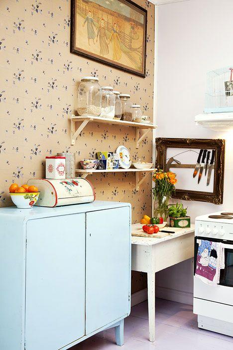 Soma keittiö. Keittiön tason virkaa hoitaa vanha kirjoituspöytä, ja astiat ovat löytäneet paikkansa vanhasta liinavaatekaapista. Pihlgren & Ritolan pehmeäsävyinen Kaneli-tapetti on hyvä tausta tunnelmalliseen keittiöön. / How cute is this kitchen! / Kuva/pic: Petra Tiihonen