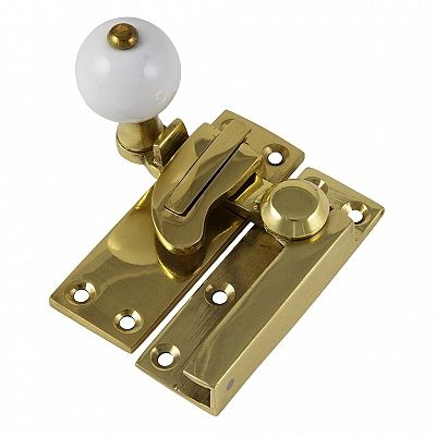 Swing arm sash window fastener with lock.  Brass with white porcelain knob.  Makes an attractive addition to your home while being perfectly practical.  Available without lock also.  #crowncity #sashwindowfastener