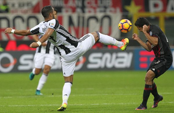 Medhi Benatia of Juventus FC competes for the ball with Carlos Bacca of AC Milan during the Serie A match between AC Milan and Juventus FC at Stadio Giuseppe Meazza on October 22, 2016 in Milan, Italy.