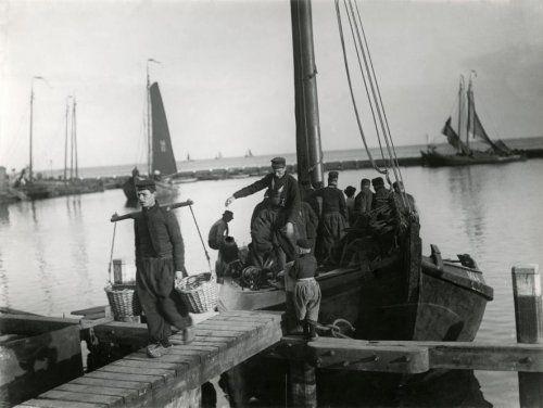 Vissersboot in de haven van het eiland Marken wordt uitgeladen door middel van manden aan een juk, jaren '30.
