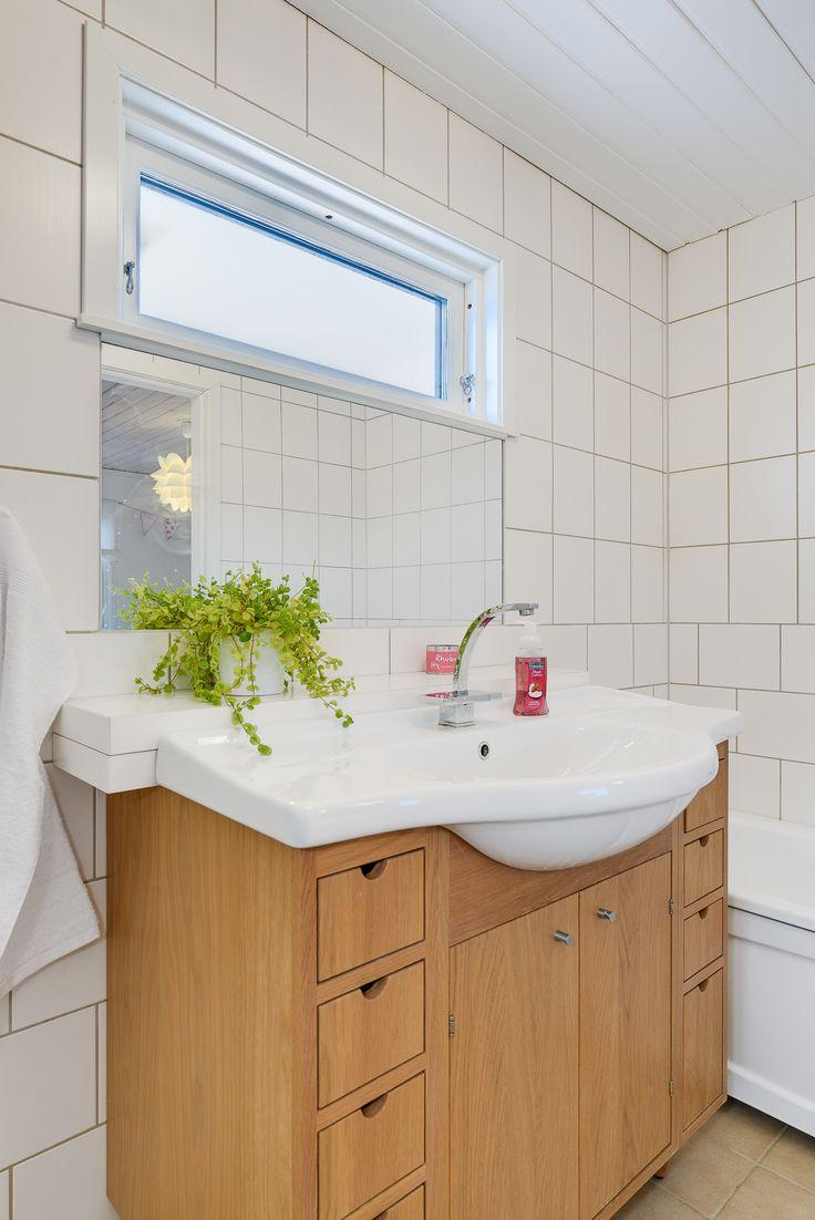 Praktisk badrumsförvaring och fönstersättning som inte stjäl väggyta.