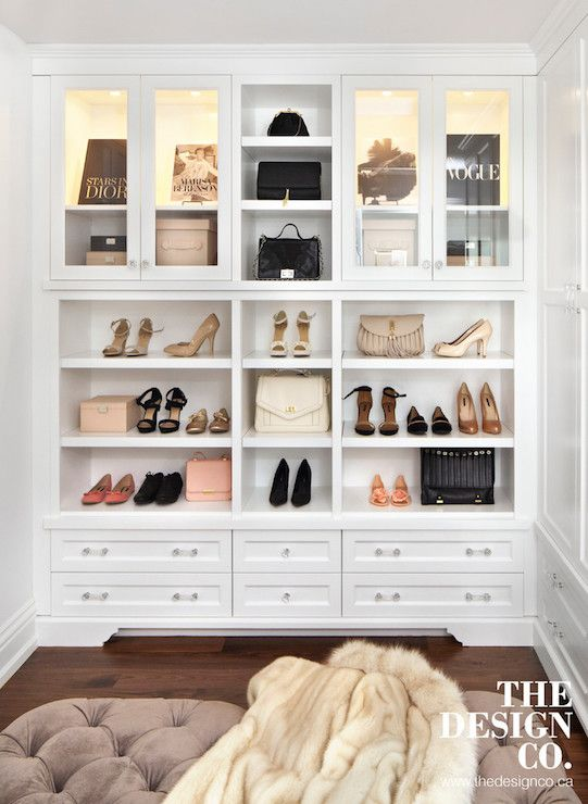 Glam walk-in closet features tray ceiling accented with a glass and nickel chandelier with crystal droplets illuminating a brown velvet tufted ottoman flanked by built-in wardrobe cabinets. The back of the walk-in closet boasts glass front display cabinets filled with designer bags illuminated by custom lighting stacked over cubbies filled with shoes and storage drawers accented with glass pulls.