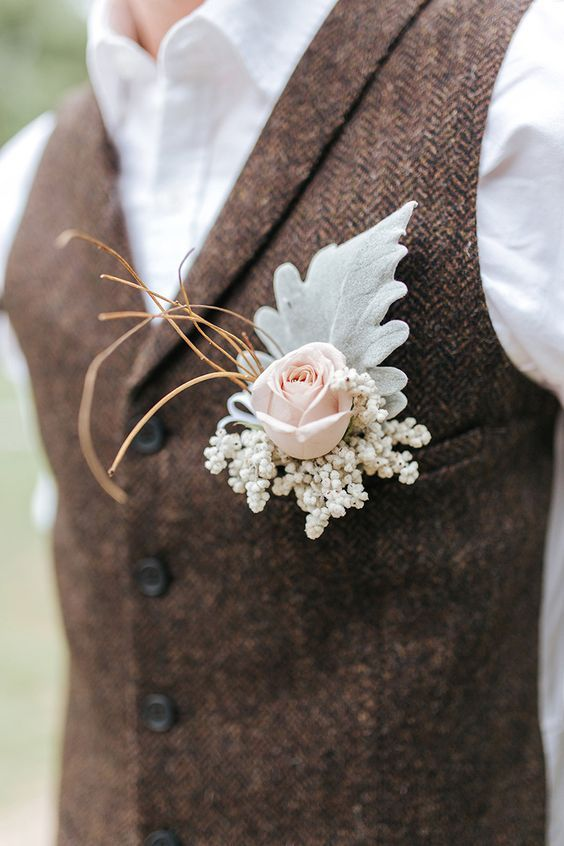Groom wearing brown vest with blush rose and dusty miller buttonhole, rustic boh…
