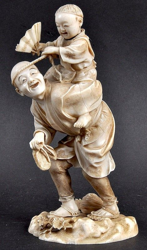 A 19TH CENTURY JAPANESE MEIJI PERIOD IVORY OKIMONO depicting a male in a shagreen jacket holding aloft a boy. Signed tablet. 6.25ins high.