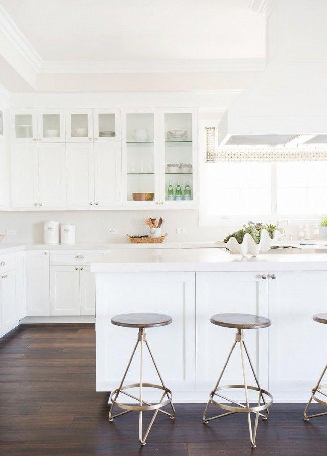 An All White Kitchen With Dark Wood Floors And Mosaic Backsplash
