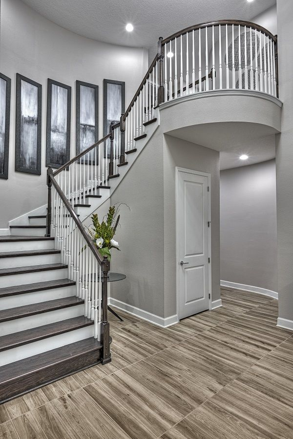 A dramatic staircase welcomes guests to this exquisite home in Orlando, FL | Harmon plan by Richmond American