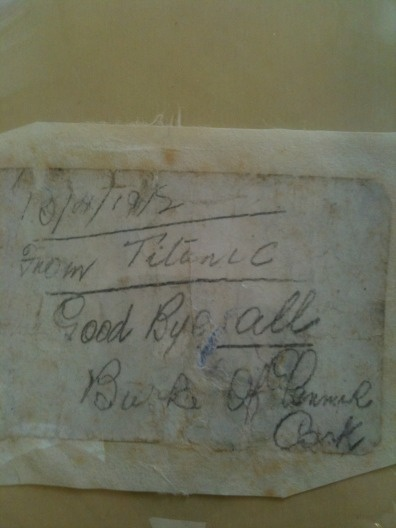 """A note written by Jeremiah Burke, 19. The message was put in a holy water bottle which was thrown overboard by a Titanic victim while the ship sank. The note reads """"From Titanic, goodbye all, Burke of Glanmire, Cork""""."""