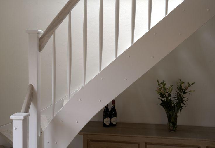 Vitmålad trappa med steg och handledare i ask.