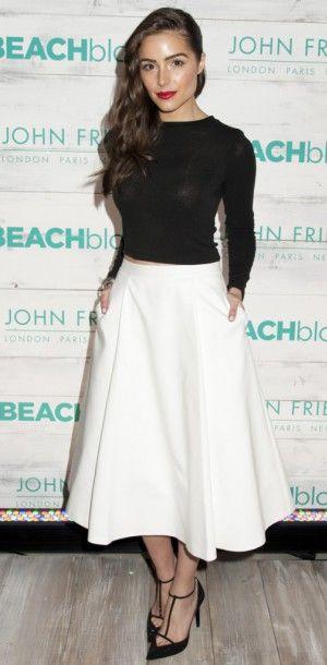 Olivia Culpo : un look sage, féminin et élégant. Haut court noir à manches longues, jupe taille haute blanche évasée longueur midi