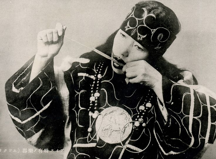 Ainu woman playing the Mukkuri, Hokkaido, Japan, ca.1920. The player vibrates the tongue cut out of the bamboo by pulling one of the strings, while holding the instrument in front of the mouth. Volume and tone colors are changed by changing the shape of the mouth.