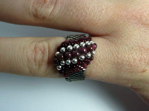 Este anillo llamativo es tejida a mano con múltiples tamaños de granos, que van desde granos de diminuto tamaño 15/0 color acero Delica a esferas de 4mm de granate. Los siete granates en el centro flanqueados por esferas plateadas y cilíndrica de color rojo oscuro y granos de la semilla. El esquema de color funciona igualmente bien para los hombres o las mujeres. Este anillo es aproximadamente un tamaño de los E.E.U.U. 9 o 10 y 60 mm de circunferencia.