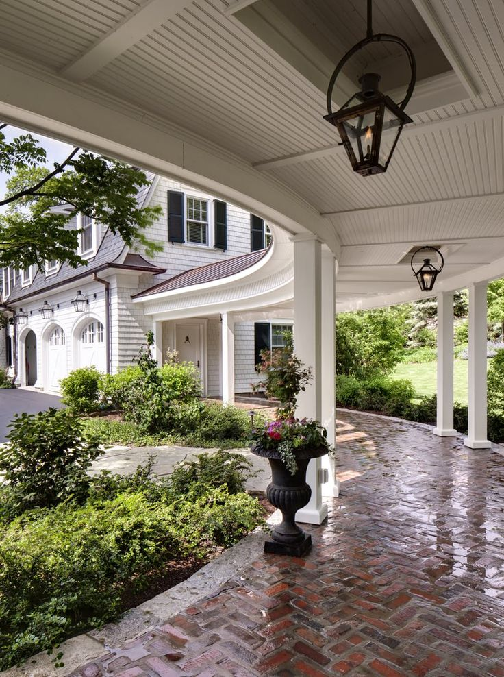 a classic loggia paired with a beautiful brick walkway and lush landscaping by wade weissmann