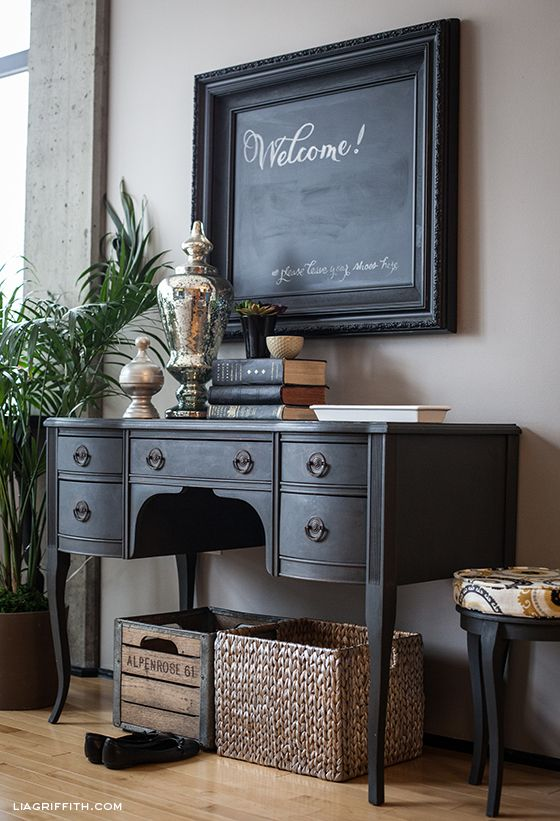 Ornate second-hand frame and a piece of foam board cut to fit inside were both painted with chalkboard paint to create this cute entryway sign.
