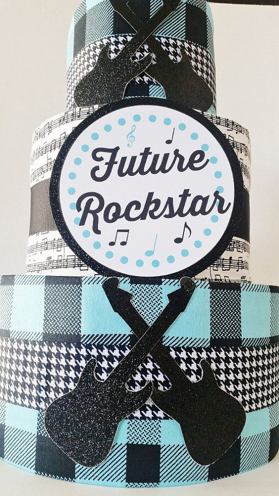 This Rock a Bye Baby themed diaper cake centerpiece is the perfect decor for a Boys Rock or Future Rock Star themed baby shower. This diaper cake has 3 tiers that are made up of 60 size 2 high quality diapers. All of the diapers in this diaper cake are 100% usable and is both a one of a kind and practical gift for the parents to be. This diaper cake is make with coordinating black and blue fabric and is adorned with glitter card stock guitars. This diaper cake comes wrapped in tulle and…