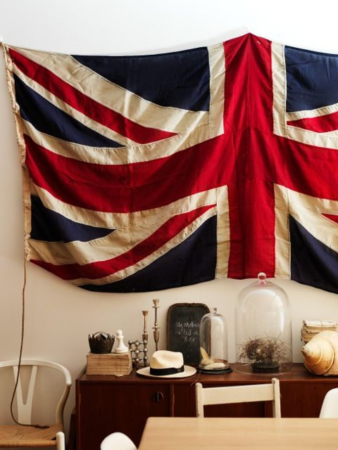 Union Jack above a sideboard with unique finds and treasures (via The Society by Sibella Court)