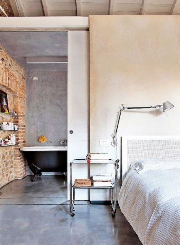 mooi ontwerp, schuifdeur naar de badkamer, eenheid in materiaal op het plafond de wand en de vloer, Italiaans stuc in een licht grijze tint mooie combinatie met de ruwe bakstenen muur.