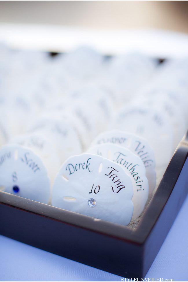Perfect for the beach wedding.  Sand dollar escort cards. Sand Resort / via StyleUnveiled.com