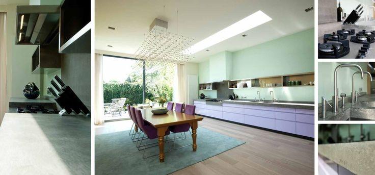 Moderne keuken MDF gespoten in kleur met verlaagd kookgedeelte waarin een Pitt Cooking kookplaat in geïntegreerd. Betonnen aanrechtbladen en achterwand bij kookplaat en dubbele RVS spoelbakken en RVS bovenkasten - The Living Kitchen by Paul van de Kooi