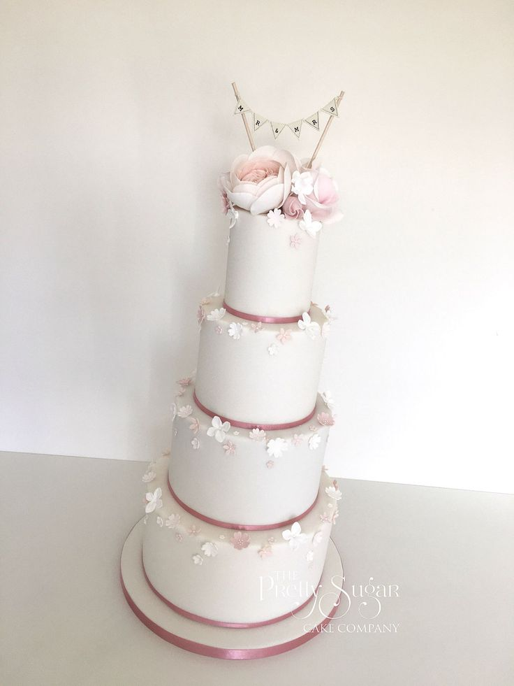 Blush pink and softest peach sugar roses wedding cake with cascading blossoms