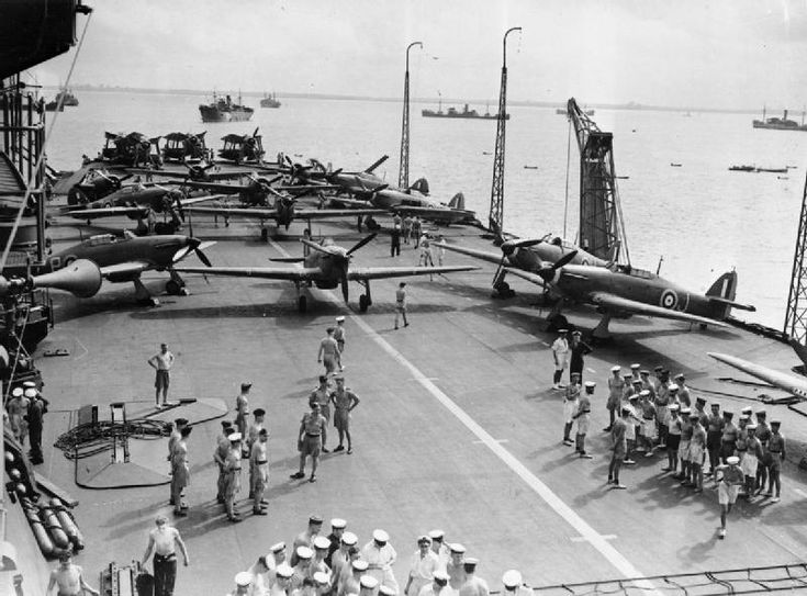 HMS INDOMITABLE, Hawker Sea Hurricanes and Fairey Albacores on the flight deck during a Malta convoy. Note the radio masts in the upright position and the crane on the edge of the deck.