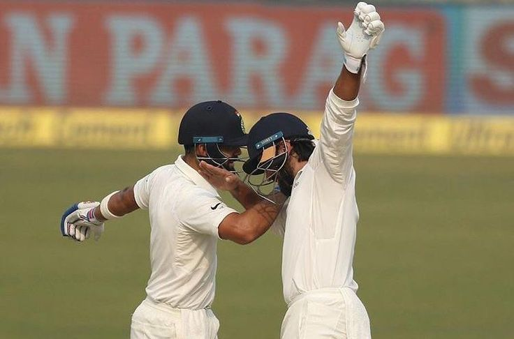 Indian cricketers celebrate after scoring 100 runs