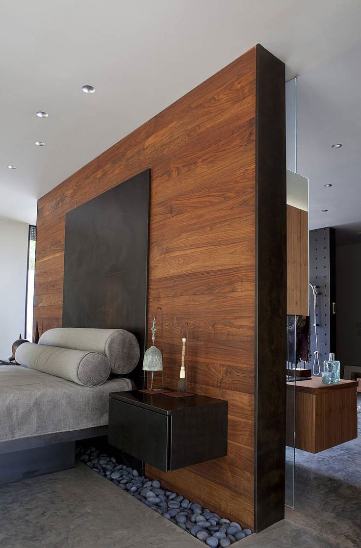 master bedroom Floor with rock insert glass between room and bathroom wood on the bed wall pot light above bed