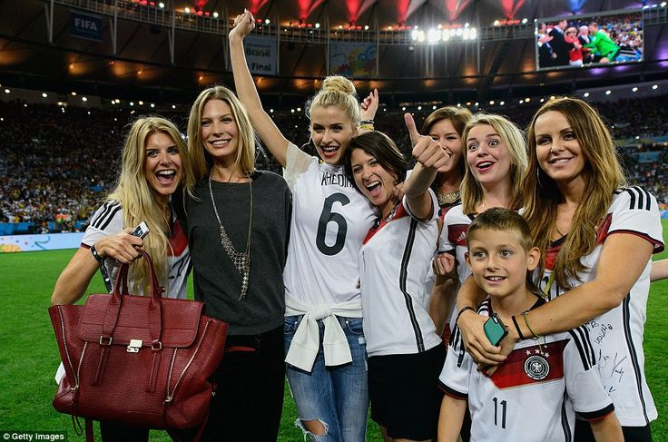 German Wags, from left, Lisa Rossenbach, Sarah Brandner, Lena Gercke, Kathrin Glich, Lisa Wesseler and Sylwia Klose and her son invade the pitch to help their men celebrate victory