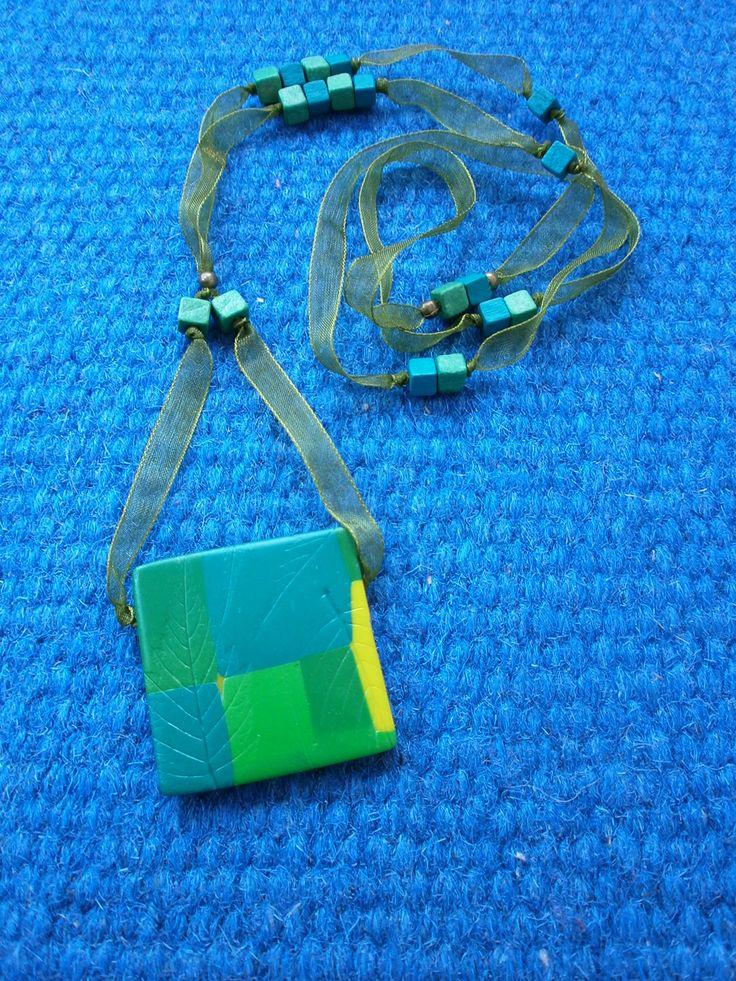 Podzimní otisky Náhrdelník - čtverec z fimo hmoty v zelených odstínech s otisky listů na saténové šňůrce s dřevěnými korálky.  Rubová strana je tmavě zelená s otiskem listu.  Délka šňůrky je cca 42 cm, čtverec je cca 3,7x3,7 cm, bez zapínání.