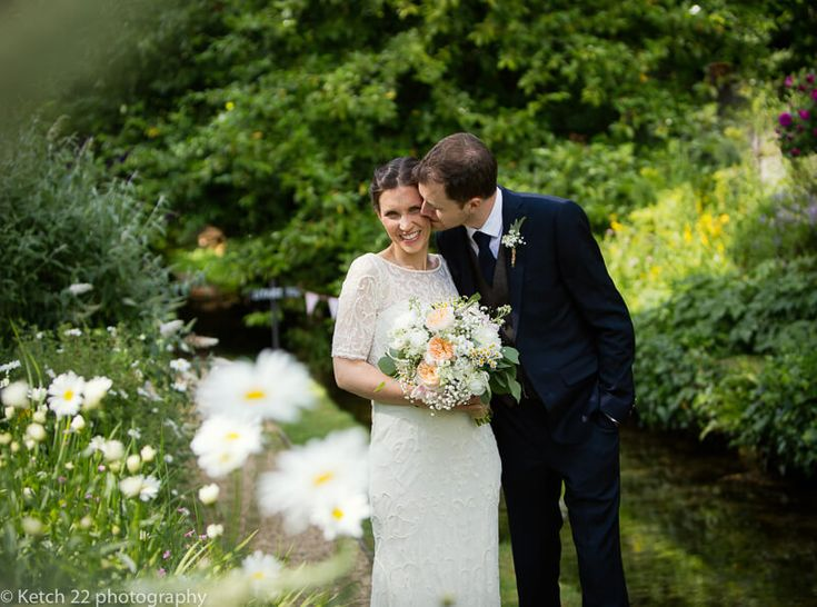 Groom kissing bride in beautiful Cotswold garden at wedding in Gloucestershire