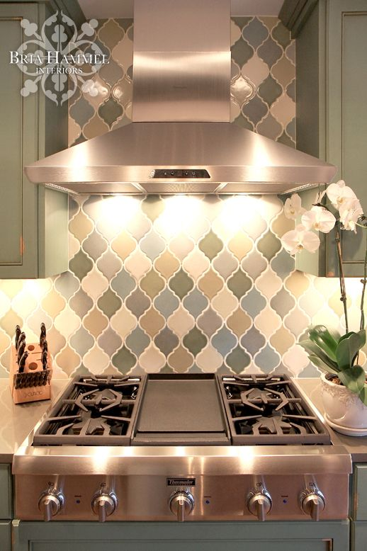 COLOUR PALETTE: Hand Glazed Arabesque Tiles Form An Artful Backdrop Behind  The Sleek Stainless Steel Range Hood In This Neutral Transitional Kitchen.