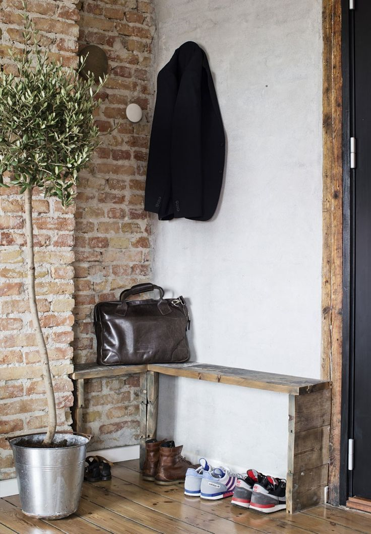 Rustic entryway featuring a brick wall and a custom built wooden bench.