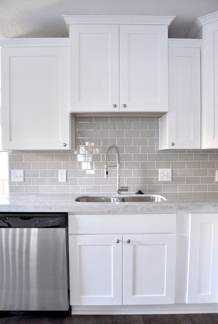 Smoke Gray glass subway tile, + carrera marble + white shaker cabinets, pull down faucet + stainless appliances