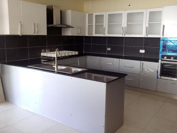 Fitted Gloss White and Grey Kitchen CAbinet with Black Granite top and appliances.