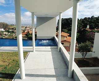 A marquise que cobre a varanda  avança sobre pequena faixa da piscina
