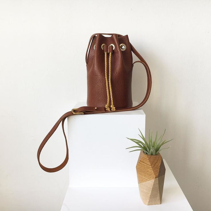 Mini bucket now available in tan in our online shop standing proud here next to a beautiful woody creation from @broadwaymarket buddy @jamie_gaunt  #bucketbag #minibag #newin #stylewatch #londonmakers #madeinbritain #broadwaymarket #carv