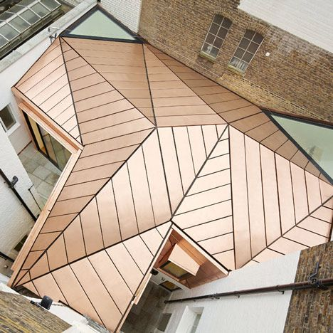 Office extension with a faceted copper roof by Emrys Architects