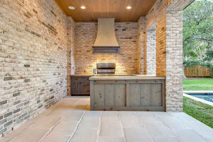 Beautiful patio kitchen boasts distressed cabinets topped with natural stone countertops and a built-in BBQ under a wood paneled vent hood situated across from a distressed island.