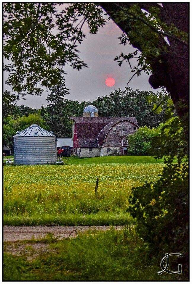 Orange sun dipping behind barn