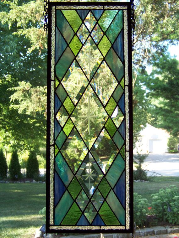 "Measures approximately 83/4"" x 23 3/4.    This panel has hanging loops on all four corners and can be hung horizontally or vertically to suit the window space you have available.    The center focal point of this panel consists of three diamond bevels with etched starbursts (or crosses or flower, whatever your preference of name might be) in the center of each.    Surrounding these three diamonds and medium and small clear beveled diamonds.    Also surrounding the center diamonds are colored…"