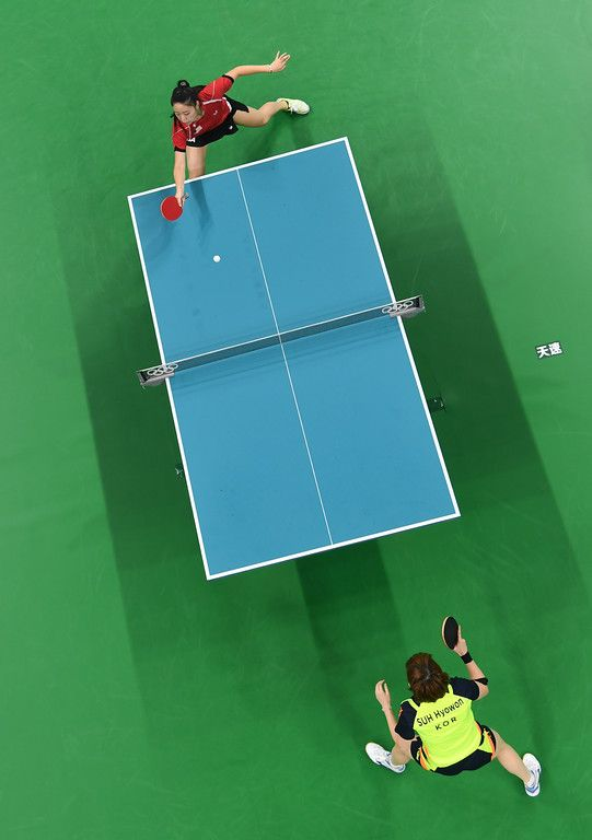 . An overview shows USA\'s Lily Zhang (top) playing against South Korea\'s Suh Hyowon in their women\'s singles qualification round table tennis match at the Riocentro venue during the Rio 2016 Olympic Games in Rio de Janeiro on August 8, 2016. (ERIC BARADAT/AFP/Getty Images)