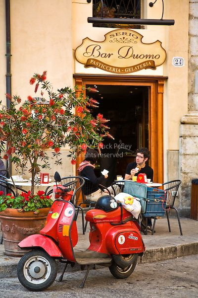 Couple eats breakfast at outdoor table, their red Vespa motorscooter parked at curb in front of the The Bar Duomo, Pasticceria and Gelateria, Piazza Duomo, Cefalu, Sicily, Italy