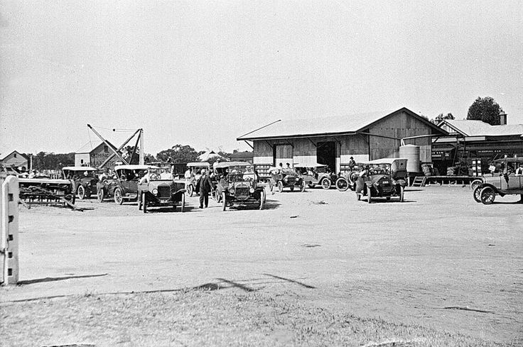 View of a motor vehicle parking area at Rainbow Railway Station and rail yards. Several motor vehicles are in the foreground. Behind them the station buildings are visible. Two vehicles at front left are Model T Fords, c1920.