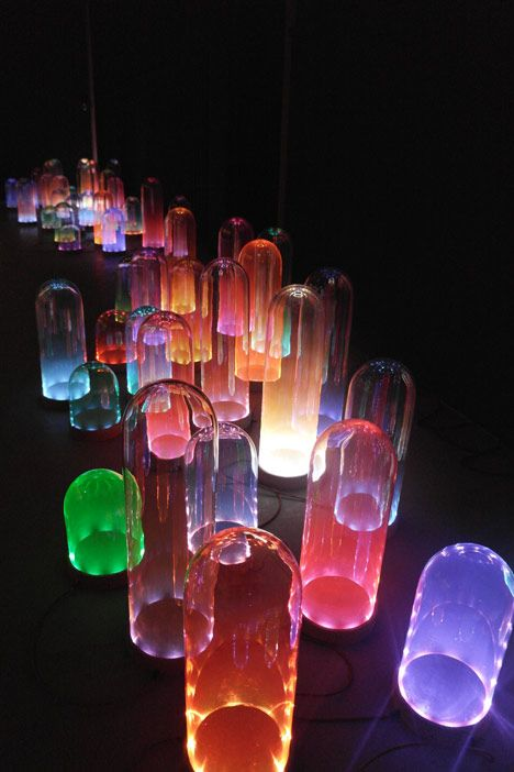 The Nola series by Ralph Nauta and Lonneke Gordijn of Studio Drift comprises tinted glass bell-jars fitted into circular cork bases, with a ring of LEDs in a contrasting colour under the rim of each glass piece.
