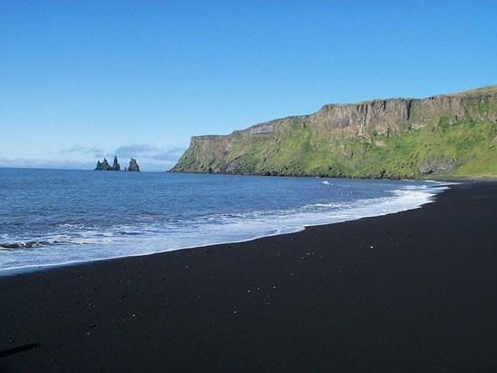 Vík Beach in IJsland is prachtig om naar te kijken: de witte golven zorgen voor een hard contrast met het zwarte zand en de vreemde rotsformaties in de verte creëren een mysterieuze sfeer. Volgens een oude legende zijn het versteende trollen die gevangen werden genomen door de zon. Het groene mos op de omringende bergen geven het landschap een zachte toets.