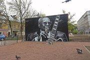 Би Би Кинг. Санкт-Петербург, 2-я Советская улица, д.1.  Портрет легендарного блюзмена появился в Греческом сквере спустя неделю после его кончины. «Король блюза» изображен в привычном для себя благостном расположении духа. В его руках любимая гитара Gibson ES-355 по прозвищу Люсиль. На прилегающей стене промышленного здания, которое украсило граффити, художники привели справедливое высказывание Би Би Кинга об образовании, как о замечательной вещи, которую у человека невозможно отнять.