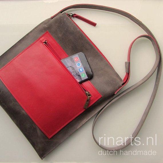 Minimalistische, stevige, toch elegant! Past uw iPad, de iPad Mini, en uw iPhone 6 plus en veel andere dingen! U kunt meer lezen het over de geboorte van dit ontwerp op mijn blog: http://www.rinarts.nl/blog/made-present Deze tas SQR (plein) in ontwerp Kleurenblok: -grijs-bruine koe lederen geboend. Deze leer veroudert prachtig! -rode metalen rits, met een luxe donker messing rits trekken en rode lederen detaillering -grote drop-in zak, groot genoeg om te dragen van uw i...