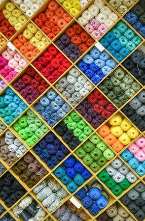 gomitoli di lana: Filati o sfere di lana e si stanno formando bel modello colorato. Accessori per merceria in un negozio di tessuti scaffali. Multi immagine colorata. Archivio Fotografico
